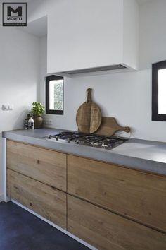 И снова игра на контрасте холодного бетона столешницы и теплого деревянного фасада в современной кухне.