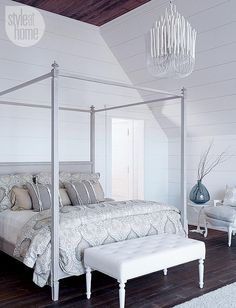 Coastal Bedroom. Coastal Bedroom Lighting Ideas. In the master bedroom, a soft grey, white and taupe palette keeps the four-poster bed from looking too dramatic, especially when paired with an equally riveting chandelier made of tapered wood pieces. Via Style at Home. #Bedroom #Lighting #Chandelier