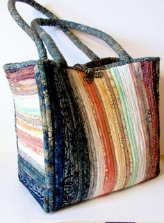 A variety of batik fabric strips have been wrapped around cotton clothesline and sewn together to form this attractive large tote bag. Bag has two large pockets inside and a brass button closure. Made from quality Anthology batik fabric in coordinating pastel and dark colors. Completely handmade. 11 x 11 x 6