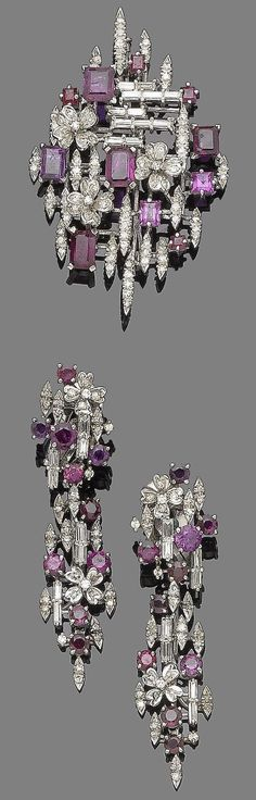 A ruby and diamond brooch and earring suite.  The navette-shaped openwork brooch of geometric and floral design, set throughout with baguette and single-cut diamonds, accented with graduated step and square-cut rubies, accompanied by a pair of pendent earrings en suite, diamonds approx. 1.65cts total, lengths: brooch 6.0cm, earring 5.9cm