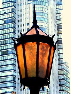 Recostada en la modernidad de un vidriado edificio, la vieja farola atesora sus historias de tango y malevaje mientras sus luz amarillenta, por el tiempo, sigue alumbrando orgullosamente enhiesta.
