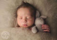 Newborn in wool fluff & britches and bonnets bunny lovie.  Portrait Pretty Photography is a baby photographer servicing all of WNY in-studio or on-location for posed or lifestyle offering Newborn Photography Buffalo