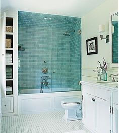 Cool way of having shower over bath for a small bathroom - I like the blue tiling and the 'alcove' and shelving next to the bath
