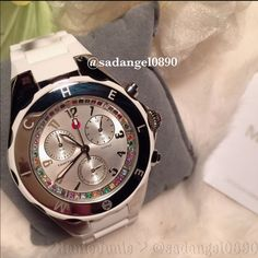 NEW MICHELE TAHITIAN JELLY BEAN WITH CRYSTALS Stainless steel Caseback: Stainless steel, screw-down Bezel: Stainless steel set with crystals Dial: Silver Hands: Silver Markers: Silver Arabic numerals Features: Chronograph Strap: White rubber Clasp: Pin buckle Crystal: Sapphire Crown: Pull-push Movement: Swiss quartz Water resistance: 5 ATM/50 meters/165 feet Case measurements: 40 mm wide x 40 mm long x 12 mm thick Strap measurements: 23 mm wide x 8 inches long Box measurements: 5 inches wide…
