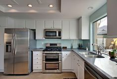 Traditional Kitchen with Aristocraft Cabinetry - Teagan Slab - White, Complex marble counters, limestone floors, Subway Tile