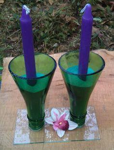 Un Candelero muy lindo hecho a partir de dos copas de botella color verde, dos candelas y arena para peceras. La base es un rectángulo de vidrio.