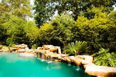 Turquoise-blue water fills this pool, and assorted rocks line the edge and form waterfalls down the side. Framed by exotic plant life, this pool has a clear tropical design.