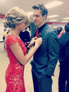 This adorable prom couple is so perfect! This red prom dress features a sexy lace bodice and form-fitting style.