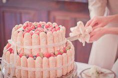 Source: 500 days of weddings  Ça faisait longtemps que je n'avais pas posté un truc qui donne envie de dire MIAM MIAM.  En voilà une idée qu'elle est bonne: Une charlotte géante enrubannée pour gâteau de mariage!… Oui vous commencez à le savoir, je suis pas super fan du wedding-cake.  La charlotte de compét' aux biscuits rosés, rehaussés par quelques fruits rouges, c'est joli ET appétissant.