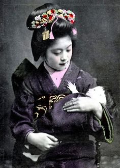 """Maiko with doll. Under Old Japan's patriarchal system, young girls, the lowest ranking humans, were sold by their families to the """"pleasure quarters."""" Pleasure for the male clients. Misery for the female inhabitants."""
