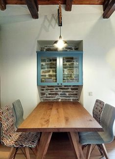 Dinner table at a remodelled old stonehouse. Backless glass cupboard.