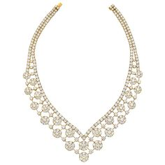 """Diamond """"Snowflake"""" necklace, designed as an openwork bib necklace composed of a series of diamond-set 'snowflake' clusters, the clusters alternating with single circular-cut diamonds, each joined by knife-edge gold links, to a band of articulated circular-cut diamonds, the full necklace including 346 circular-cut diamonds weighing approximately 72.77 total carats, mounted in 18k yellow gold, numbered NY59139, signed Van Cleef & Arpels. 21st century"""