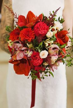 A bold red bouquet comprised of garden roses, dahlias, and lilies, created by Il Profumo Dei Fiori.