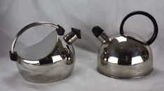 2x WMF Designer Kettles Kettle Left Carlo Giannini, Italian designer whistling kettle. Produced 1980s. Made of stainless steel with an elegant curved handle and characteristic form.  THIS IS NOT AN ELECTRIC KETTLE, FOR USE ON STOVES  Kettle Right WMF Cromargan® whistling kettle. Produced 1990s 2L Cromargan® 18/1 stainless steel kettle with a black, circular handle. THIS IS NOT AN ELECTRIC KETTLE, FOR USE ON STOVES