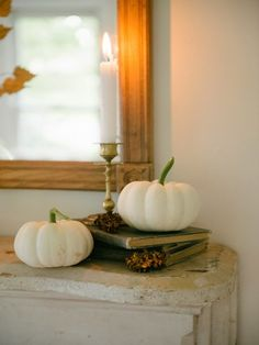 Prop up pumpkins with books and flank them with candlesticks on your mantel for fall.