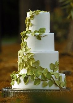 Round white wedding cake with green sugar vine crawling up the tiers.WOW maybe less green tho and some light pink little flowers