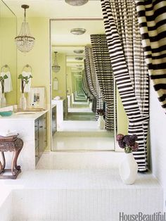Striped palazzo curtains in Victoria Hagan fabric from Holly Hunt hang on either side of the sunken tub in the master bath of this Michael Berman-designed Los Angeles home. They offer a graphic counterpoint to the Dunn-Edwards Perfect Pear paint on the walls and ceiling.