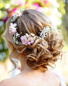 Bride's casual loose curled bun with flowers wedding hair
