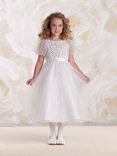 Satin and tulle tea-length A-line dress with illusion tulle puff short sleeves, satin bodice features tulle overlay encrusted with beaded motif of tiny three-dimensional satin flowers, covered buttons down back, satin set-in waistband with tieback sash, full gathered multi-layer tulle skirt with wire scalloped edge, ideal as First Holy Communion or party dress. Sizes: 6 [...]