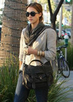 Jessica Alba Leather Shoulder Bag  Jessica Alba looked California cool carrying a Proenza Schouler PS1 bag. The weathered looking black leather flap front bag was the perfect purse for hitting Beverly Hills shops.  Brand: Proenza Schouler