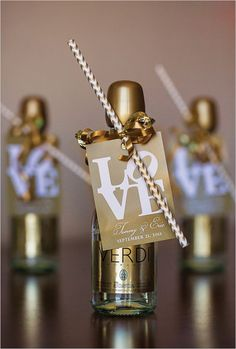 A wedding favor /escort card. Mini champagne bottles with sipping straws and cute love labels. Captured by: Rhinehart Photography #weddingfavors #goldwedding