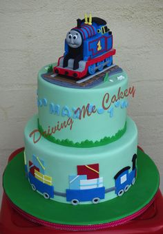 Two tiered Thomas The Tank Engine birthday cake with hand modelled Thomas cake topper. Find me on Facebook (Driving Me Cakey) for more photos of my work or contact me via e-mail, drivingmecakey@gm... to enquire about an order. Located Fairview Park, South Australia.