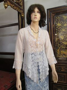 Sebuah kebaya encim antik peranakan yang terbuat dari kain paris bermotif polkadot, menggunakan jahitan opensum, dihiasi bordir krancang...