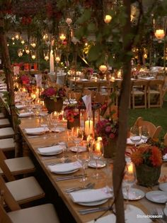 I am in love with this. The long family tables, the use of trees and coverings with hanging lights tons of candles and multiple floral centerpieces (although the centerpieces could be better)