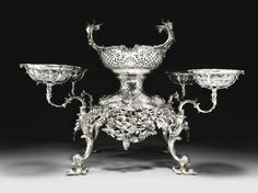 A George III silver epergne, William Cripps, London, 1757 shaped oval, on four cast supports with detachable branches, the central section rising from a cast and pierced apron of ribbon-tied flower sprays and fruit, detachable basket, crested