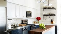 This kitchen with rich wood accents pays homage to classic American design with a subway tile backsplash and a classic blue-and-white color palette. The gorgeous butcher-block countertop adds a third surface to this small space, but instead of making the room feel disjointed, it adds an historic accent that flawlessly ties everything together.