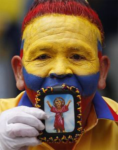 A Colombian fan kisses an image of baby Jesus before the start of a 2014 World Cup qualifying soccer match with Bolivia in Barranquilla, Colombia, Friday, March 22, 2013. (AP Photo/Fernando Vergara)