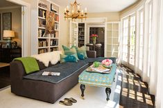 Eclectic office with gold faux bamboo chandelier, modern charcoal gray sofa with chaise lounge, turquoise blue & yellow bench, wall of French doors and bookcases.