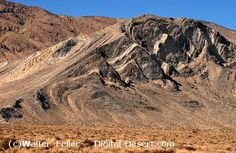 The butte in the center of the valley is composed of up-tilted beds of the Permian Butte Vly formation which are of marine origin. A large fault runs down the trend of the valley behind the butte. Butte Valley via Warm Springs Canyon. Death Vly NP, Backcountry Rds