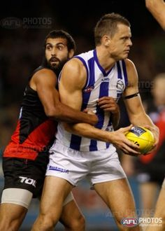 North Melbourne's Hamish McIntosh marks in front of Essendon's Courtenay Dempsey during the AFL Round 01 match between the North Melbourne Kangaroos and the Essendon Bombers at Etihad Stadium,