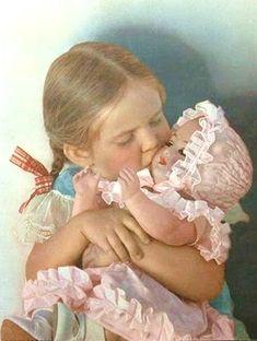 A little girl hugging her doll.