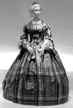 Plaid silk, European, ca. 1857. High bodice trimmed with noueds/butterfly bows; open sleeves with noueds at heading and opening; pleated skirt. Shown with collar and undersleeves. MET