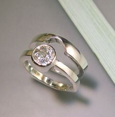 A beautiful, sparkling white topaz, bezel set in the engagement ring, and a wedding band that perfectly contours its edge! Nice!    The