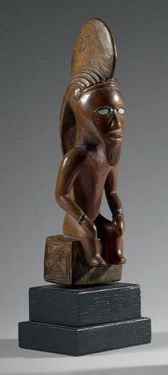 Statuette Bembe - République du Congo Bois - nacre - résine - H.: 22,5 cm Personnage assis les mains sur les cuisses au visage caractéristique de l'ethnie. Les yeux sont incrustés de nacre. - Eve - 07/12/2015