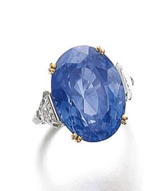 SAPPHIRE AND DIAMOND RING The oval sapphire weighing 22.99 carats, set between epaulet-shaped diamond shoulders