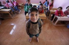 Five-year-old Omar al-Haroush poses inside a classroom in the rebel-controlled area of Maarshureen village in Idlib province, Syria March 12, 2016. REUTERS/Khalil Ashawi