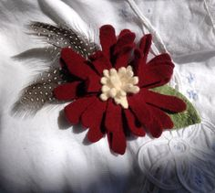 Guenia Hen feathers add class to this maroon and cream felted wool flower pin to use on a hat, lapel scarf options are endless. by UpcycleDesignsByDana on Etsy