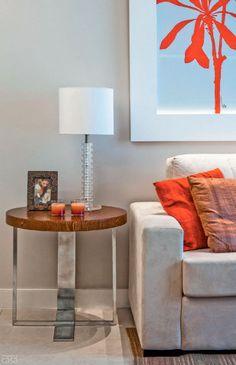 """Da medida à parceria. """"Em geral, costumo especificar uma mesa que tenha a mesma altura do braço do sofá para que os objetos sobre ela apareçam"""", afirma o arquiteto Luiz Fernando Grabowsky, do estúdio carioca que leva seu nome. A preferência é exemplificada com um de seus projetos: alinhado com a lateral do estofado, o móvel (65 x 60 cm, de aço inox e MDF com acabamento no padrão carvalho) põe em destaque o porta-retrato, o abajur e os porta-velas. O tampo redondo de madeira ajuda a aquecer o…"""
