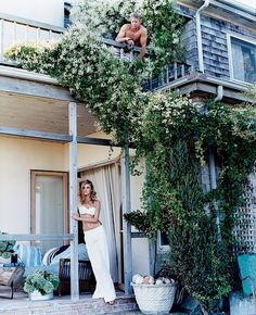 Model Caroline Trentini wears white-on-white at a beautiful beach house covered in lush greenery. Photographed by Arthur Elgort, Vogue, 2006.