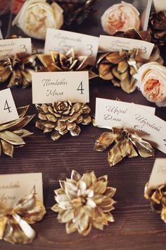 gold painted succulent escort card holders... Pine cones for fall wedding??