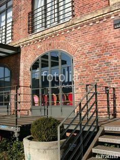 Veranda mit Eisengeländer und schönem großen Rundbogenfenster in einer restaurierten Fassade aus Backstein am Stadthafen in Münster in Westfalen in Münsterland