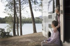 Mature couple looking out of their RV - Gary John Norman / Getty Images