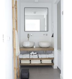 white walls, concrete basins, wood shelving, concrete-style pavers