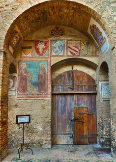 Palazzo Comunale Courtyard In San Gimignano: So many areas to explore in San Gimignano. This was in a small back courtyard of the Palazzo Comunale. Between the coats of arms, the stained and patched bricks and the door itself, you could almost hear the history. #travel #italy #tuscany