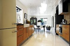 Sommerhuset er innredet i en svarthvit-stil, med glansfullt tak og gulv. Den trebrune kjøkkeninnredningen er et godt valg, og skaper en varmere atmosfære i rommet.