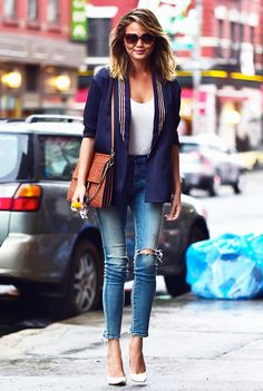 Chrissy Teigen in a navy jacket, white top tucked into distressed skinny jeans, and white pumps